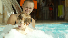 Mother holding son splashing in the rough water of the pool Stock Footage