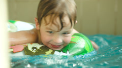 Cute child having fun swimming with rubber ring in the pool Stock Footage