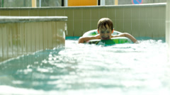 Boy with rubber ring swimming in water labyrinth Stock Footage