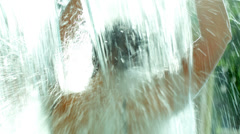 Back view of a woman in the pool under strong shower Stock Footage