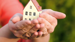 Couple holding a small toy house in hands Stock Footage