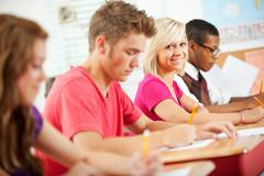 high school: smiling girl during class quiz - stock photo