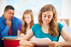 high school: girl student reading assignment - stock photo