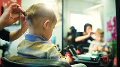 Hairdresser cutting childs hair while he playing with a toy Stock Footage