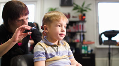Child getting a haircut from a professional hairdresser Stock Footage