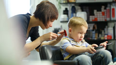 Little boy during haircut at the hairdressing saloon Stock Footage