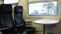 Two empty seats with table in the moving train - stock footage