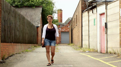 Woman in a denim shorts walks and talks towards camera like a TV presenter. Stock Footage