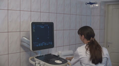 Stock Video Footage of Female doctor in hospital cleaning ultrasound machine, finishing patient consult