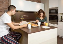 serious couple reading news in a home breakfast - stock photo