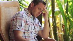 Worried man sitting in the garden Stock Footage