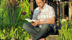 Man sitting on the stairs in the garden and reading book Stock Footage