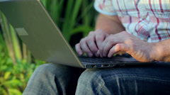 Man sitting in the garden and working on laptop Stock Footage