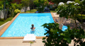 Woman Swimming in Blue Outdoor Swimming Pool. Beautiful Summer Landscape. Footage