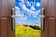 Stock Photo of open door with a view of green meadow illuminated by bright sunshine