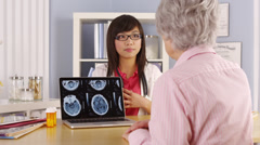 Asian doctor explaining brain scans to elderly patient Stock Footage