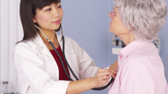 Asian doctor listening to elderly patient's heart Stock Footage