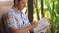 Man sitting in the garden and reading newspaper Stock Footage