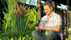 Happy man sitting in the garden and tweeting on smartphone Stock Footage