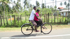 Local man and woman riding bicycle in Weligama, Sri Lanka. Stock Footage