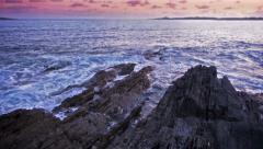 Slow Motion Waves on Rocks at Sunset Stock Footage