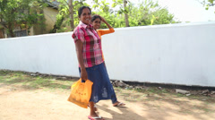 Two women walking down the street in Weligama with shopping bags. Stock Footage