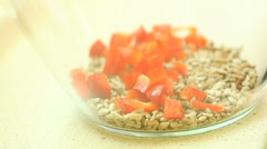 Putting slices of red sweet bell pepper into bowl with sunflower seeds Stock Footage
