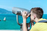 Stock Photo of man looking through binoculars at the mountains and the sea
