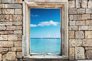 Stock Photo of wall of stones with a hole under the door on a background of a sea landscape