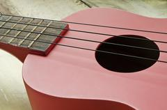 Red ukulele on wooden table Kuvituskuvat