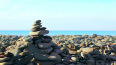 Hand putting last stone on pyramid at the seaside Stock Footage