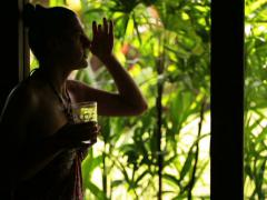 Woman talking to someone in the garden and drinking juice Stock Footage