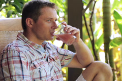 Man wiping sweat from face and drinking juice in the garden Stock Footage