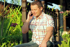 Happy man sitting in the garden and chatting on cellphone Stock Footage