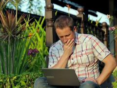 Worried man sitting in the garden and working on laptop Stock Footage