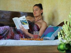Woman lying on bed and reading interesting book Stock Footage