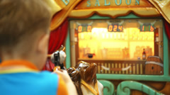Boy riding a toy horse and shooting with toy gun Stock Footage