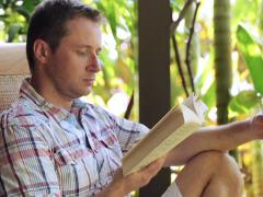 Man sitting in the garden and reading book Stock Footage