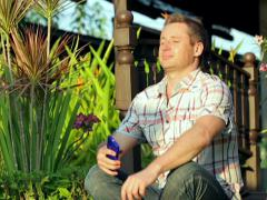 Happy man sitting in the garden and tweeting on smartphone - stock footage