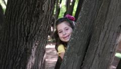 Girl hiding behind a tree - stock footage