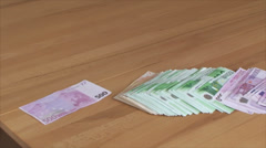 Money large and small denominations are falling on the table Stock Footage