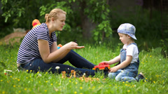 Mother and son playing outdoor on the green lawn Stock Footage