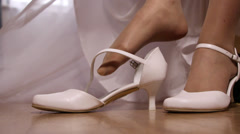 Bride in wedding dress putting on his white shoes, closeup Stock Footage
