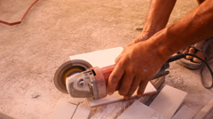 Close up of craftsman is cutting floor tile with portable angle grinder. Video Stock Footage