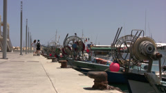Boats moored in Limassol harbor with two people walking in the distance Stock Footage