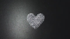 Silver glitter arrange to heart shape on black background with flying light - stock footage