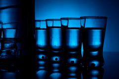 Studio shot of bottle with many glasses of vodka lit with blue backlight Stock Photos