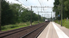 Freight train passes station Stock Footage