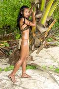 sexy indian woman holding a tree on the sand beach - stock photo