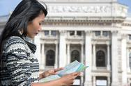 Stock Photo of young woman studying map near the burgtheater, Vienna, Austria